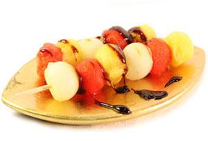 Brocheta de frutas con su jugo caramelizado